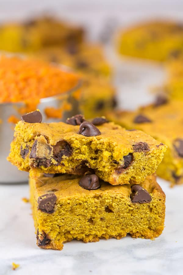 two pumpkin chocolate chip cookie bars stacked on top of each other with one bite removed from the bar on top