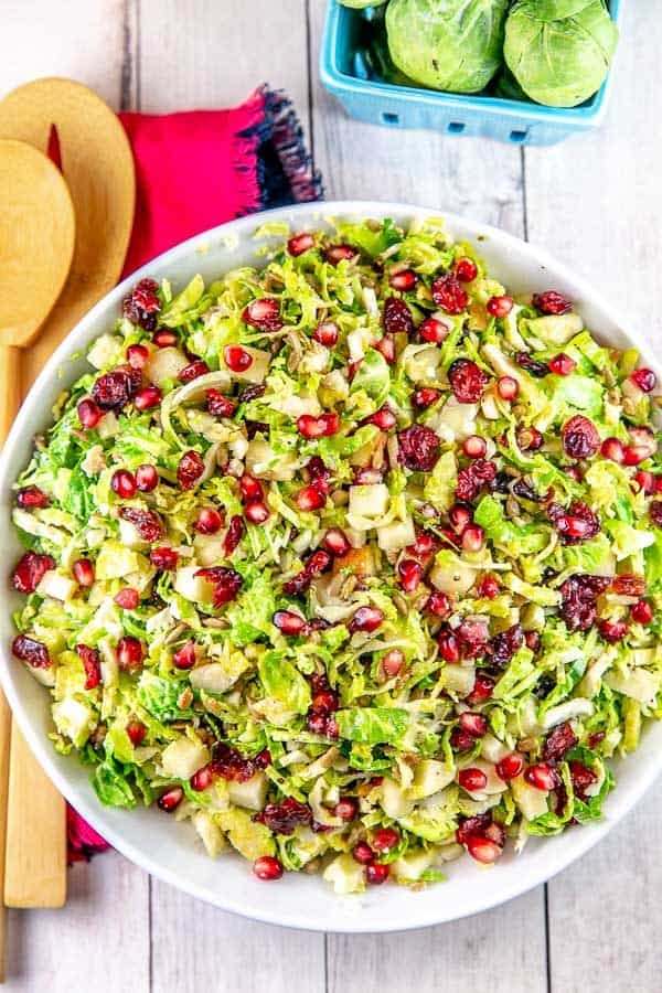 overhead view of a large white bowl filled with a shaved brussels sprout salad with apples, pomegranate arils, and sunflower seeds on a red placemat with bamboo serving spoons