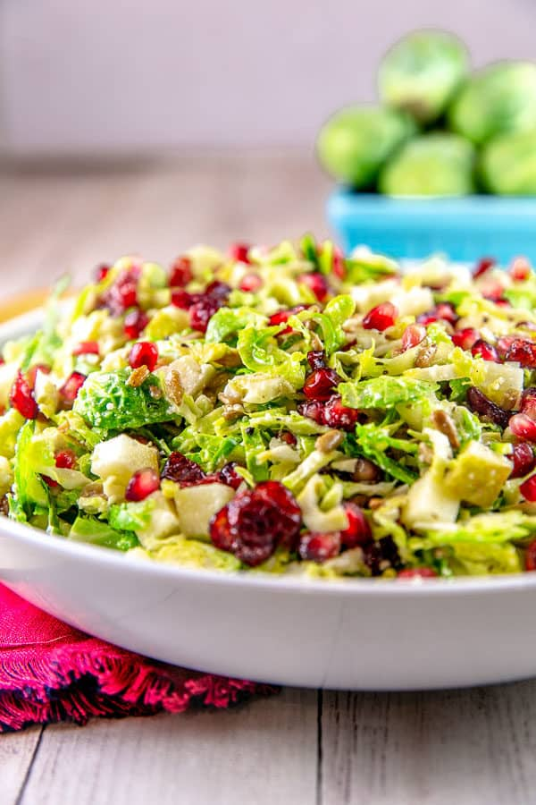 side view of a shaved brussels sprout salad piled high in a white serving bowl with whole brusslels sprouts stacked in a pint container in the background