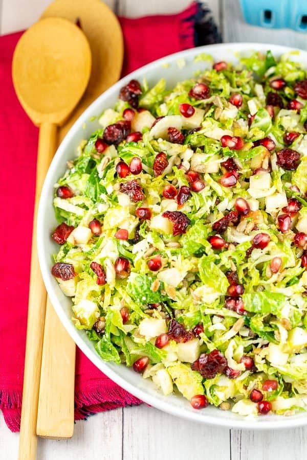 overhead view of a shaved brussels sprout salad in a white salad bowl with two bamboo salad spoons on a red cloth placemat