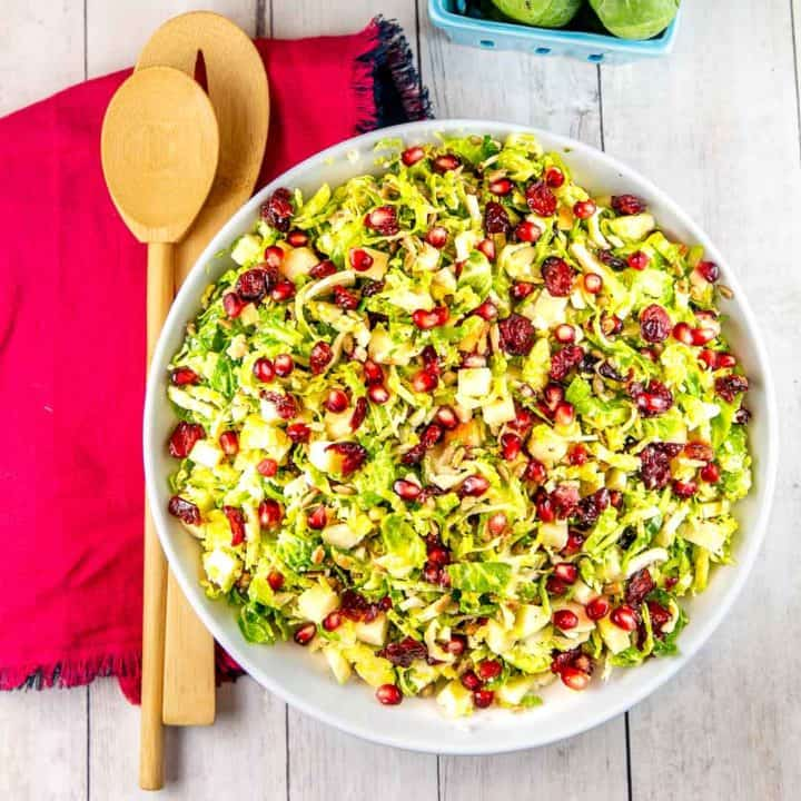 Shaved Brussels Sprout Salad: Full of shredded brussels sprouts, apples, pomegranate arils, and sunflower seeds, this make-ahead salad is quick enough for a weeknight but fancy enough for a holiday dinner. #bunsenburnerbakery #salad #brusselssprouts #vegetables