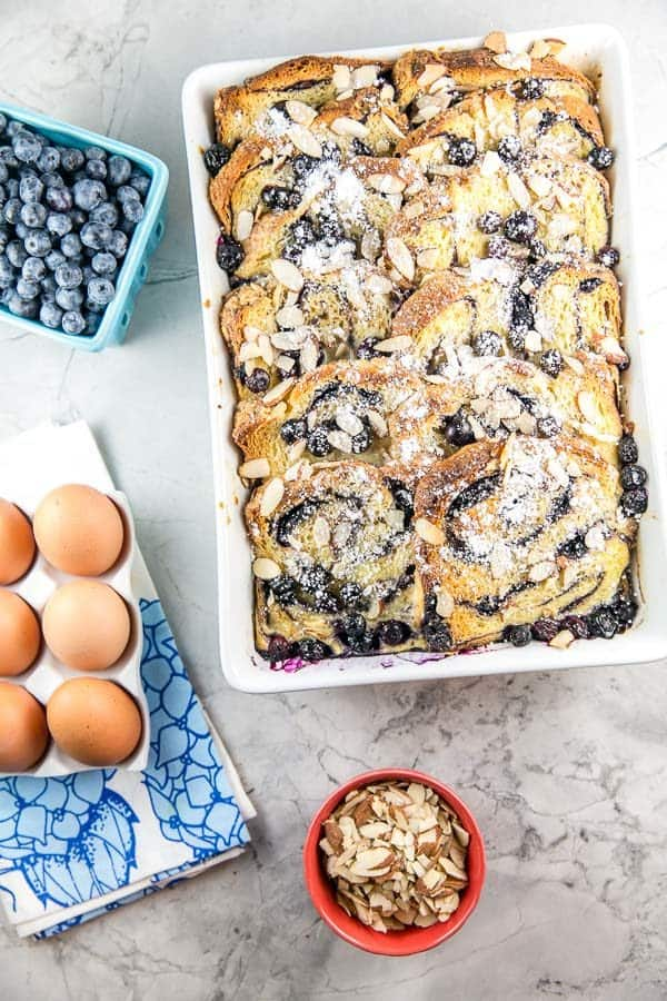 overnight baked babka french toast casserole in a white serving dish next to a ceramic container of eggs, a pint of blueberries, and some sliced almonds