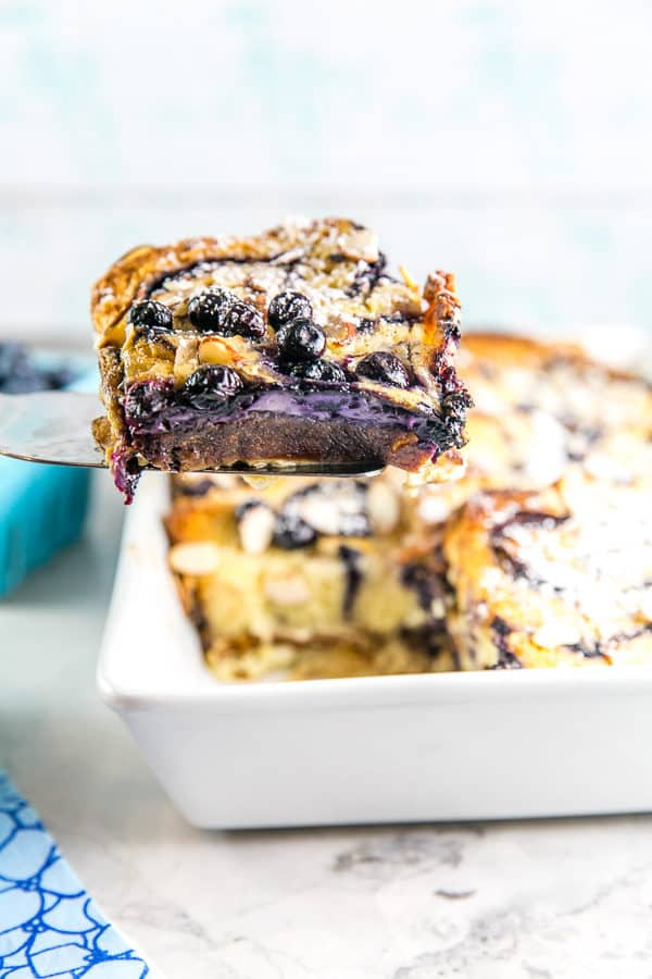 a slice of blueberry babka french toast casserole being lifted out of a white casserole dish showing a side view of a slice of the casserole