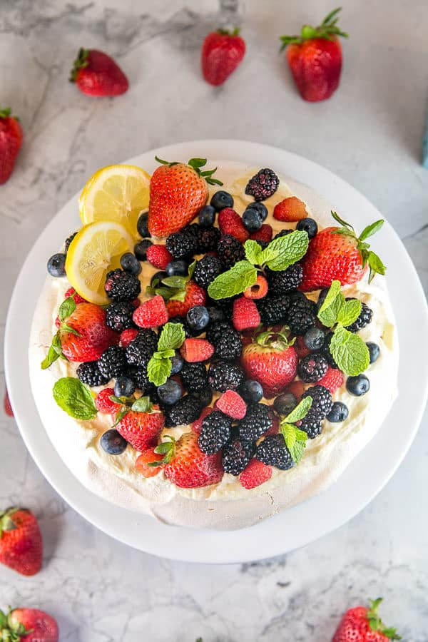 overhead view of an assembled berry pavlova with lemon curd cream piled high with fresh berries
