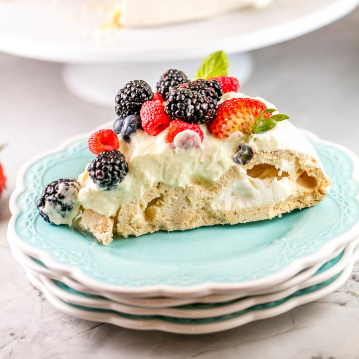 Berry Pavlova with Lemon Curd Cream: This classic pavlova recipe is the perfect entertaining dessert. Fancy enough for a dinner party, but extremely easy to make and everything can be made ahead of time! #bunsenburnerbakery #pavlova #berries #lemon #lemoncurd