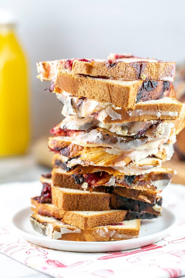 a tall stack of slices of cranberry orange babka on a small dessert plate with a jug of orange juice in the background