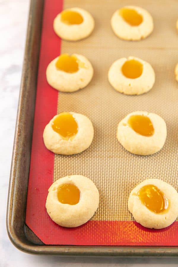 just baked lemon thumbprint cookies filled with lemon curd on a cookie sheet just golden brown with the lemon curd melted and smooth