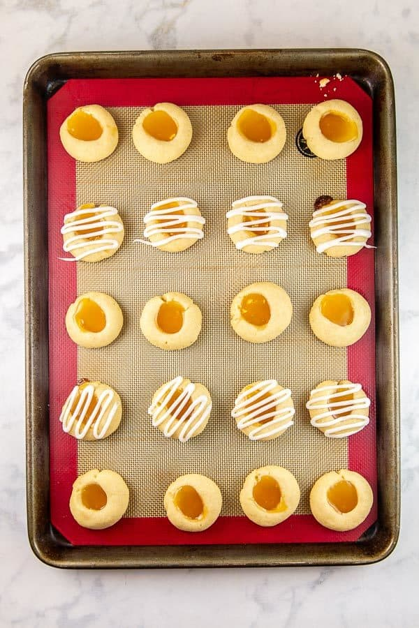 lemon thumbprint cookies on a cookie sheet alternating rows between plain and covered with lemon glaze