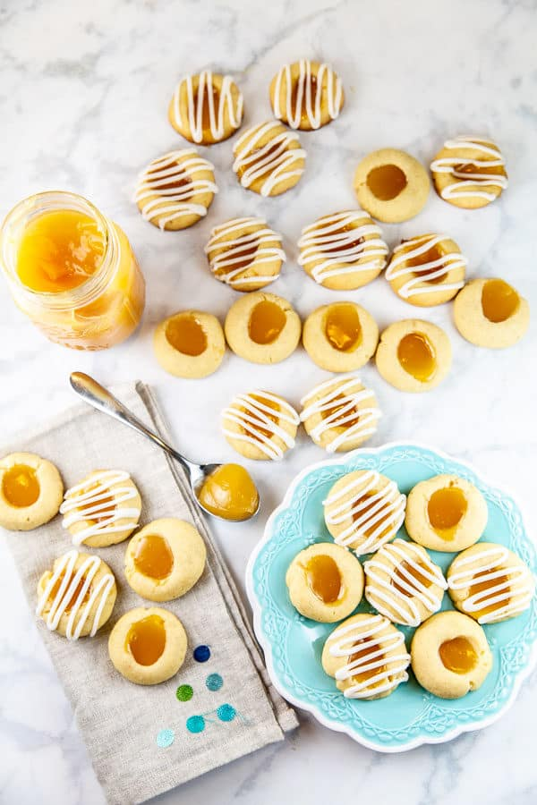 lemon thumbprint cookies covered in lemon glaze on a white marble counter with lemon curd and a blue dessert plate