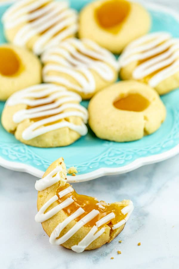 a lemon thumbprint cookie with a large bite taken out of it leaning against a blue dessert plate with a pile of cookies on the plate