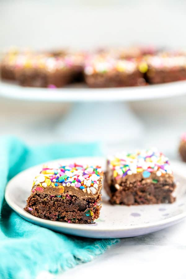two thick brownies on a plate covered in chocolate frosting and colorful sprinkles with a cake stand in the background holding the rest of the brownies