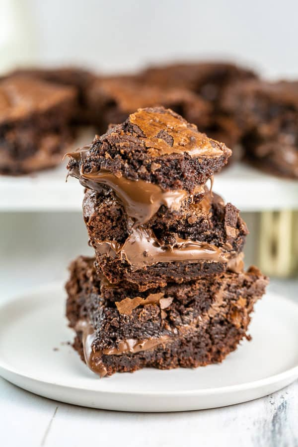 a stack of brownies stuffed with gooey nutella that is oozing out from the middle of the brownies