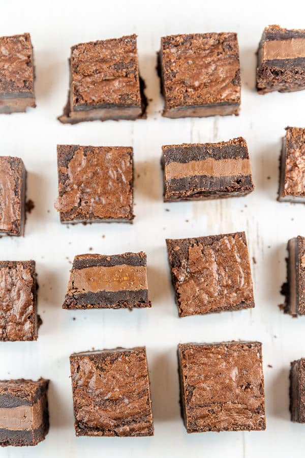 squares of nutella brownies arranged in rows with one brownie from each row flipped on its side to show a thick layer of nutella in the center of the brownie