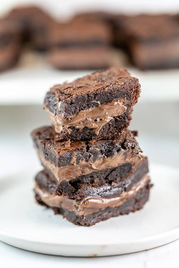 three brownies stacked on a white dessert plate with a thick layer of soft nutella in the middle