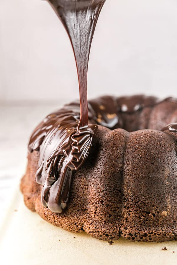 pouring thick chocolate ganache on top of a dark chocolate pound cake