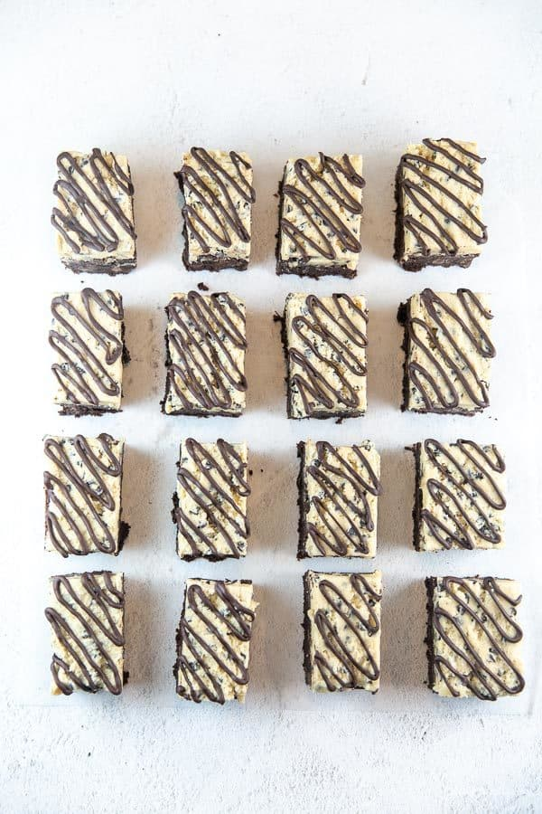 four rows of cookie dough brownies with chocolate drizzled across the top