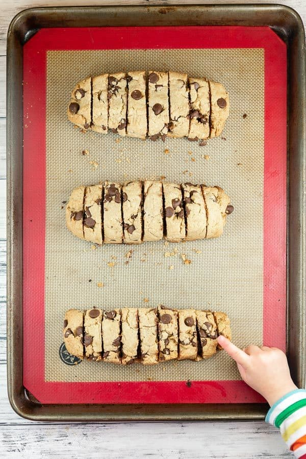 three baked loaves of mandelbrot sliced into cookies with a toddler hand reaching out to grab a cookie