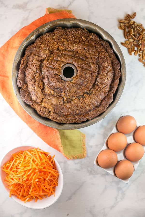 a baked carrot bund cake still in the bundt pan surrounded by carrots, eggs, and pecans