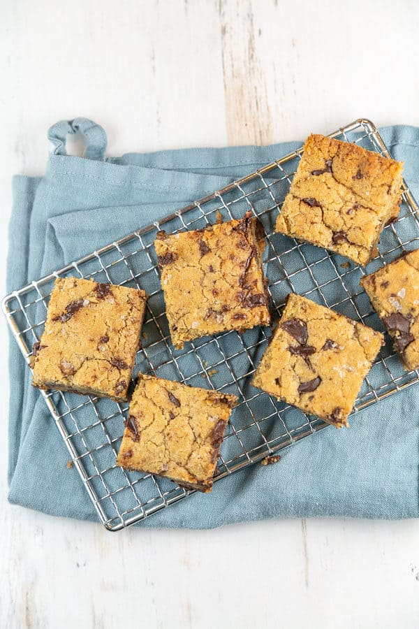 six large chocolate chip tahini blondies on a wire cooling rack