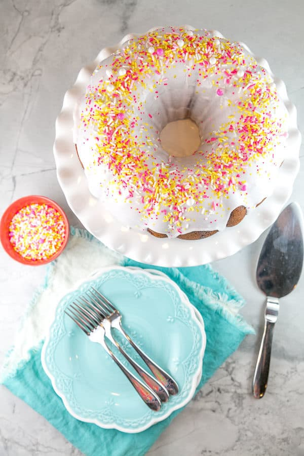 a lemon bundt cake with strawberry lemonade swirl covered in sprinkles on a white cake plate