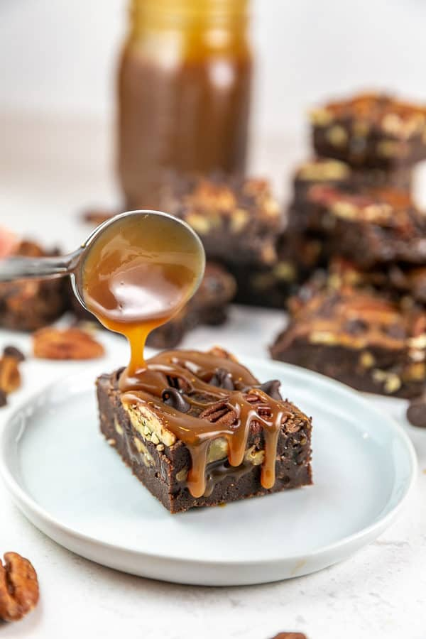 a spoon drizzling caramel sauce on a fudgy brownie