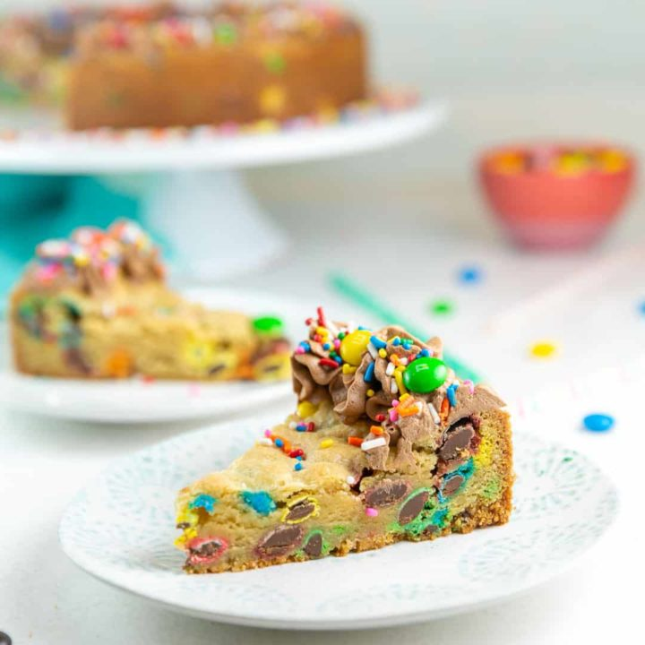 two slices of m&m cookie cake on dessert plates