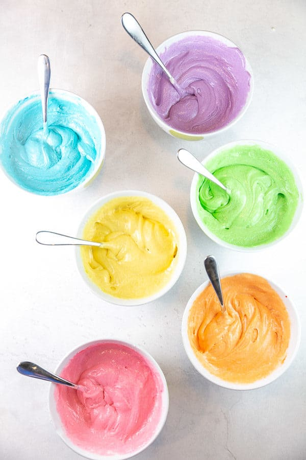 six bowls of batter dyed with food coloring