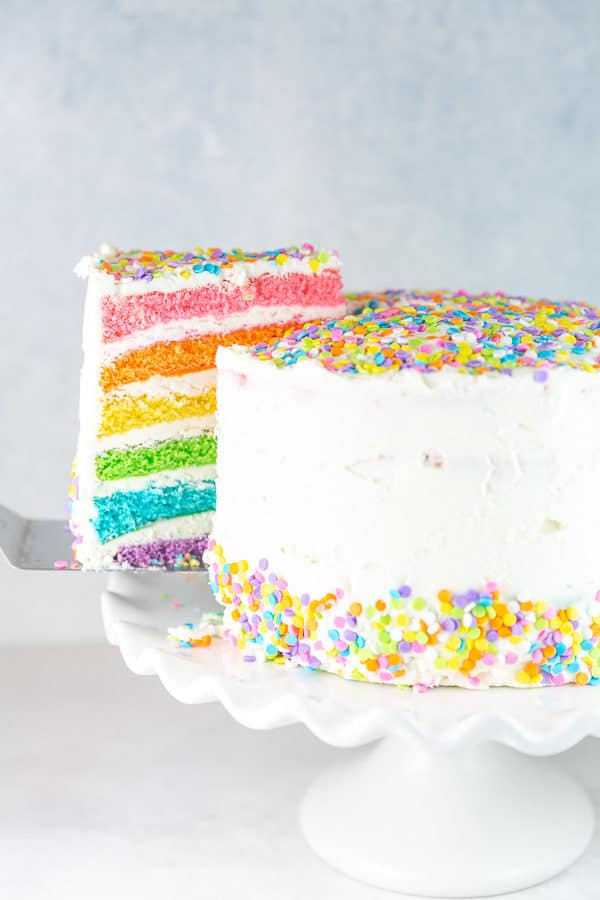 a slice of six layer rainbow cake being lifted with a cake server
