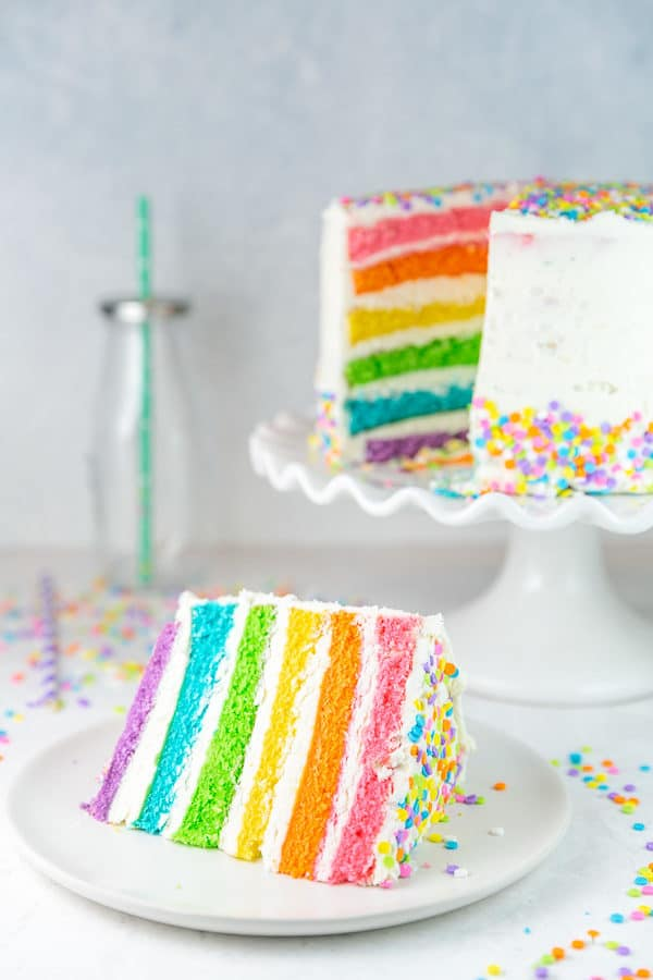 slice of rainbow cake in front of the rest of the colorful cake