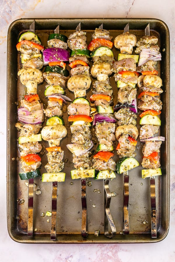long metal skewers with chicken and vegetables on a cookie sheet