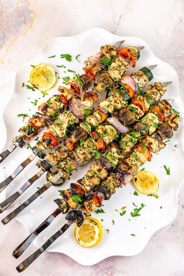 grilled kabobs with chicken and vegetables on a white serving plate