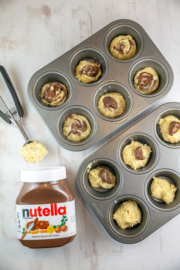 muffin tins filled with batter next to a jar of nutella