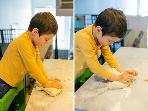 5 year old kneading dough to make pizza rolls
