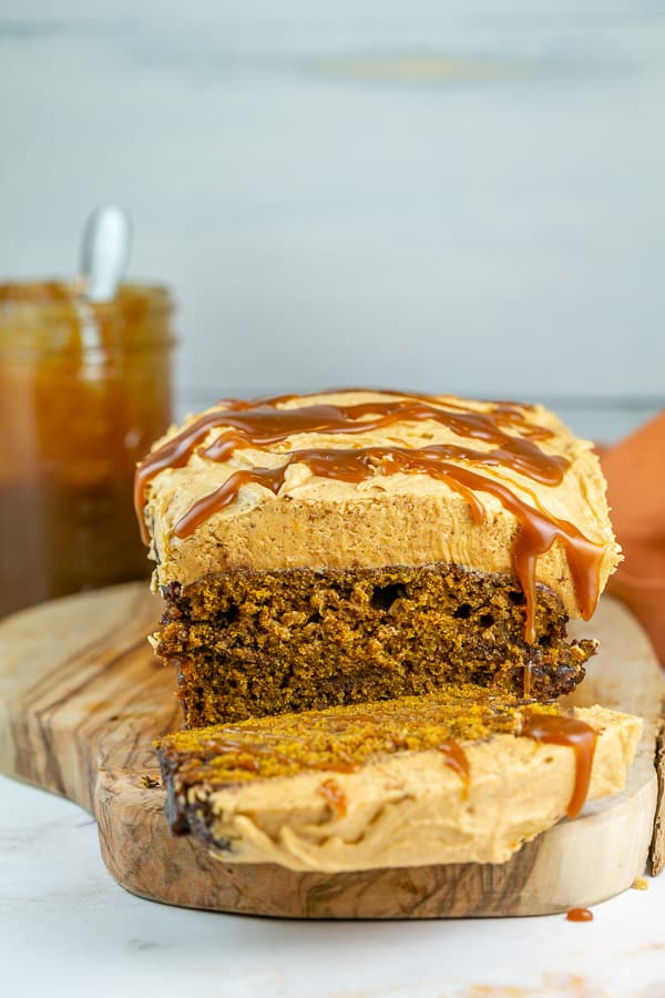 pumpkin bread with pumpkin frosting and salted caramel dripping down the side