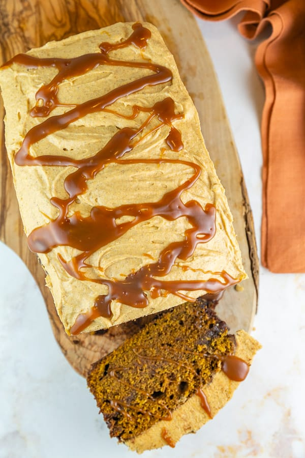 overhead view of pumpkin bread with caramel drizzle on a wooden board