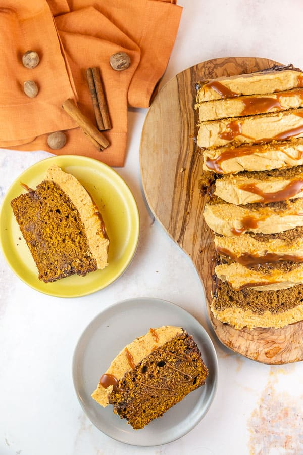 two slices of pumpkin bread with a thick layer of pumpkin frosting on small plates