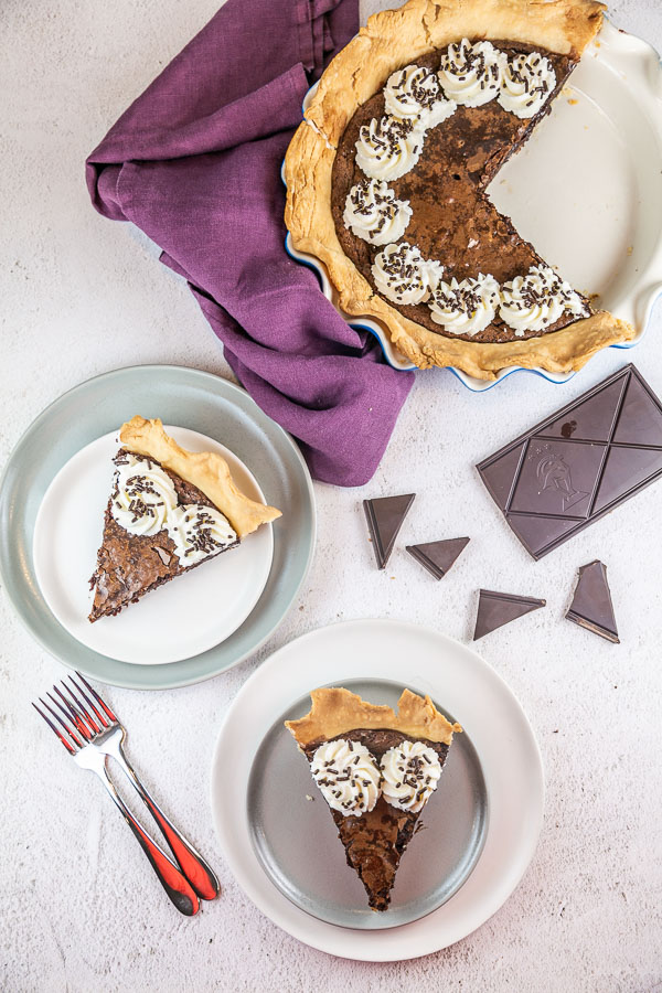 two pieces of pie on dessert plates with chopped chocolate in the background