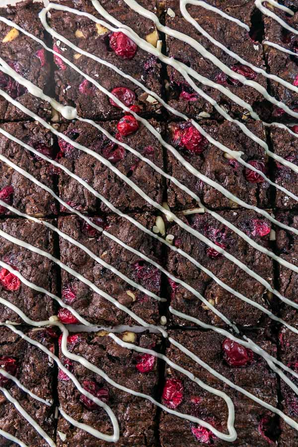 closeup of brownies with cranberries covered in a white chocolate drizzle