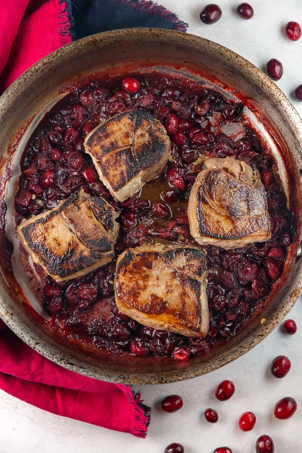four seared pork chops in a pan with a cranberry maple sauce