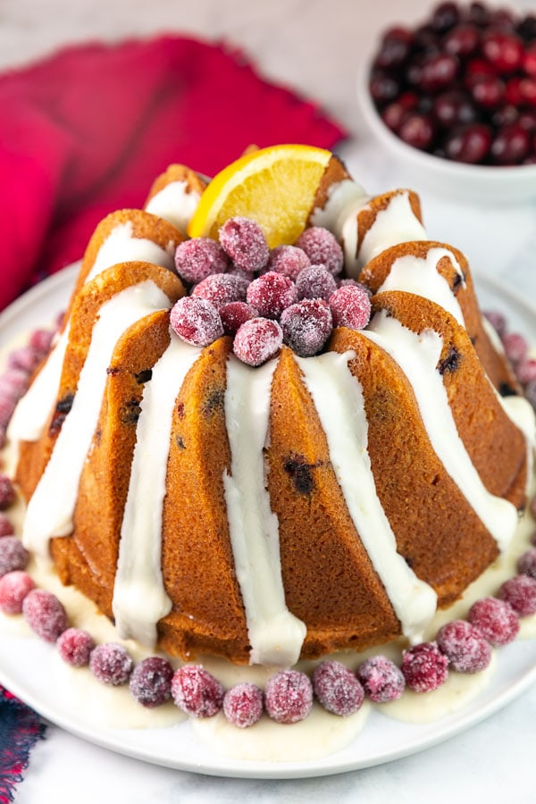 cranberry orange pound cake baked in a tall bundt pan decorated with sugared cranberries