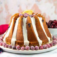 cranberry orange bundt cake decorated with orange glaze and sugared cranberries