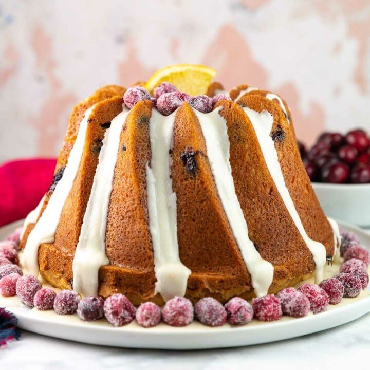 cranberry orange bundt cake decorated with orange glaze and sugared cranberries