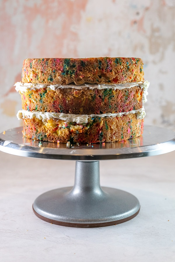three layers of cake stacked on a cake stand waiting to be frosted