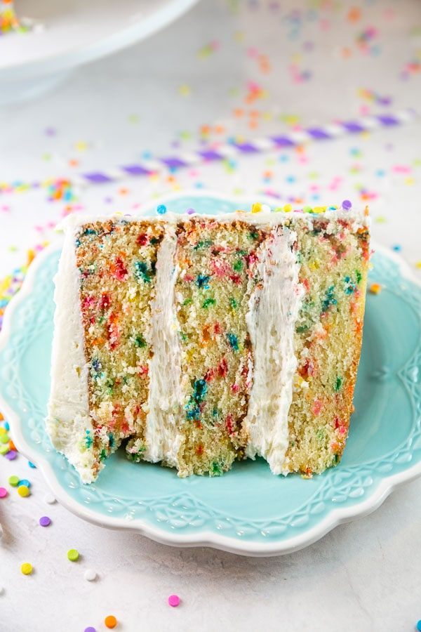 slice of three layer homemade funfetti cake on a blue dessert plate