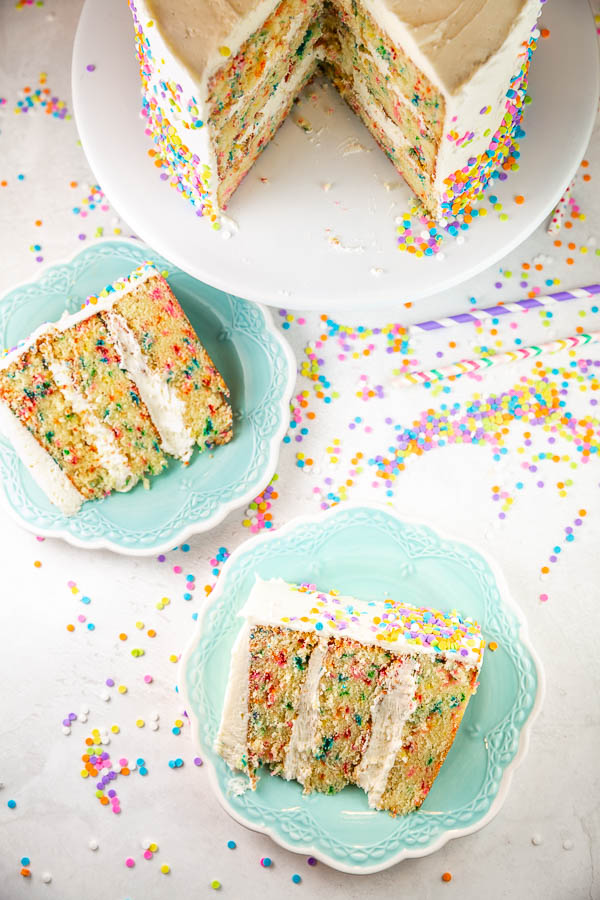 overhead view of three layer cakes on blue dessert plates with colorful paper straws