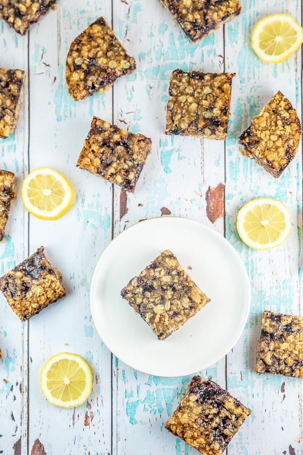 oatmeal jam bars with lemon slices on a blue and white wooden table