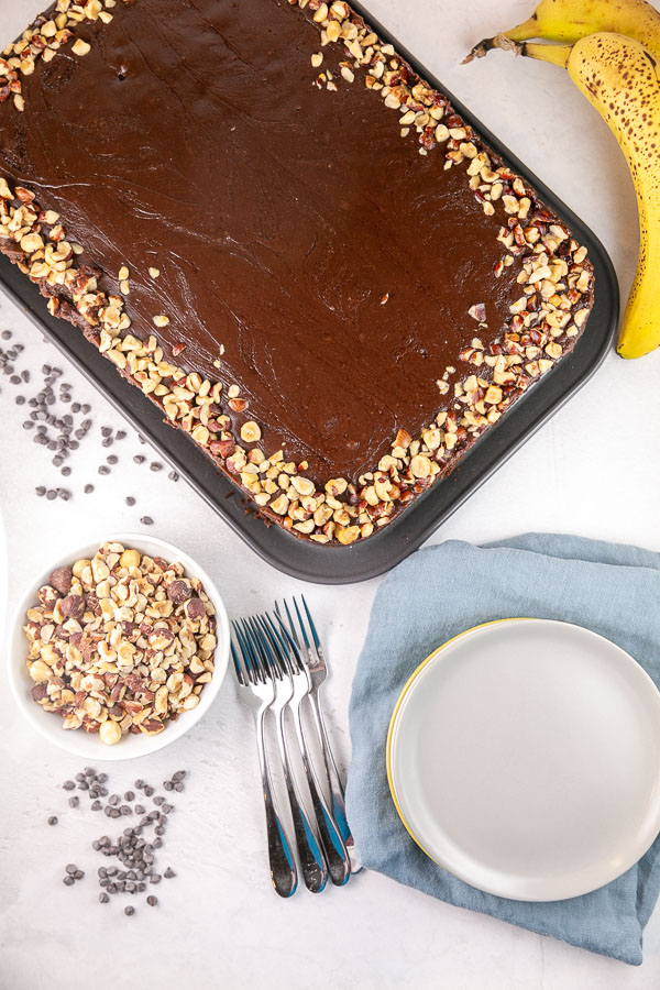 banana nutella snack cake in the pan covered with nutella glaze and chopped hazelnuts