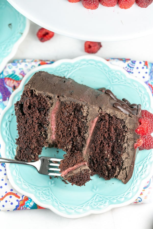 three layer chocolate cake on a plate with a fork removing one biteful