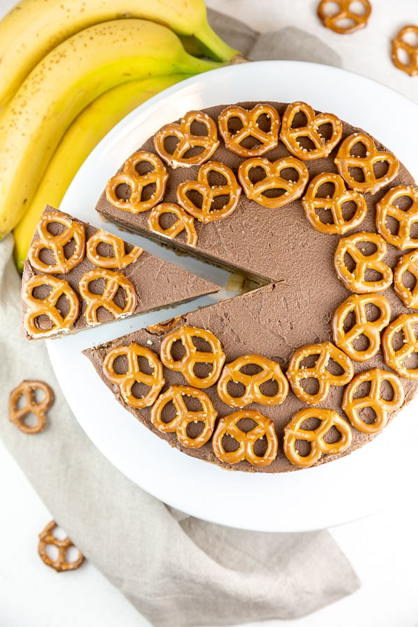 one wedge cut out and partially removed from a pie covered with pretzels on top