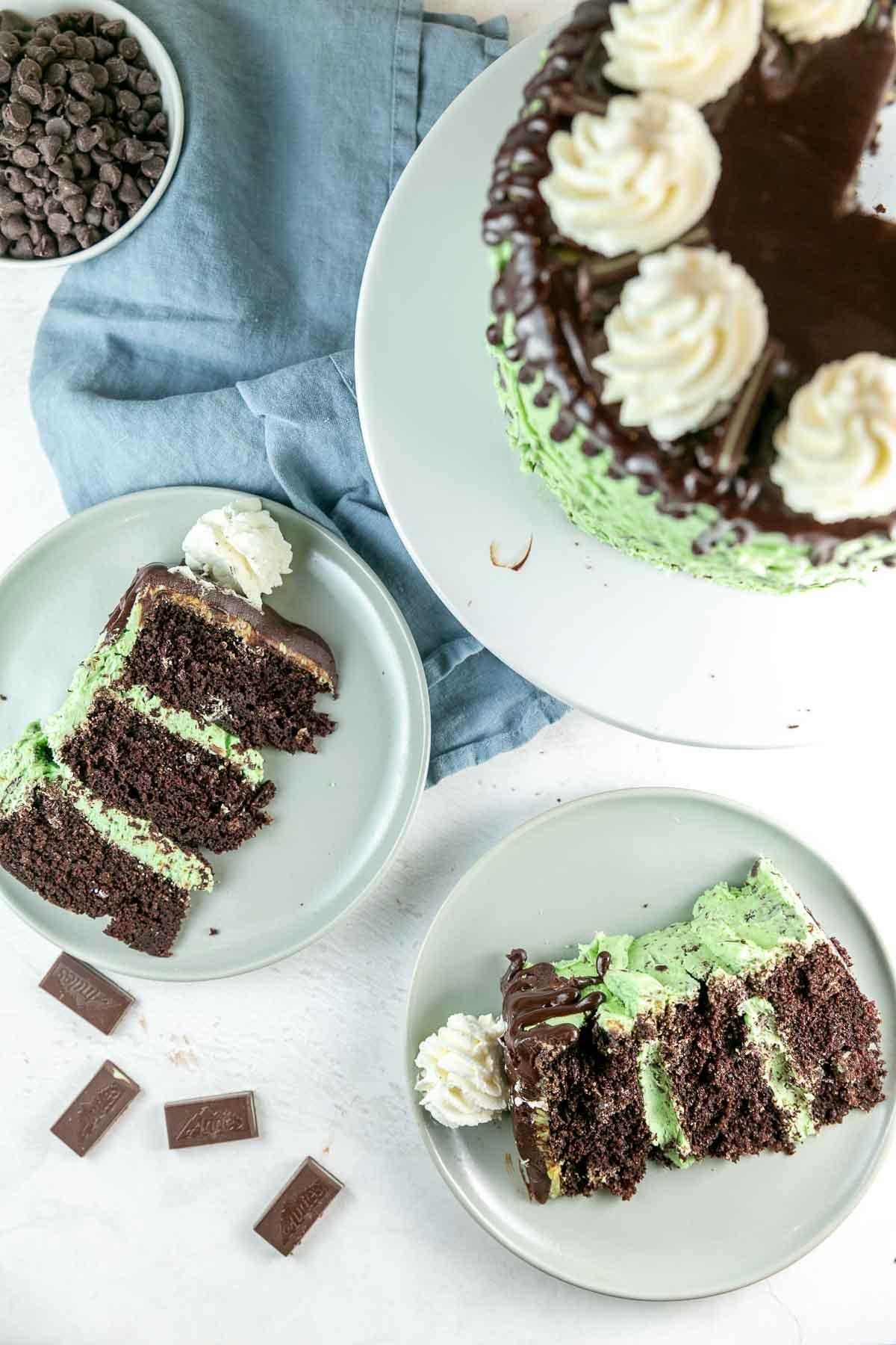 overhead view of two slices of cake on dessert plates with Andes mints scattered in the background